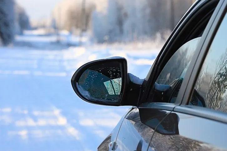 sedan car with broken mirror in winter driving